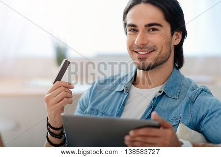 Money maker. Cheerful delighted handsome smiling man holding credit card and using tablet while sitting on the couch