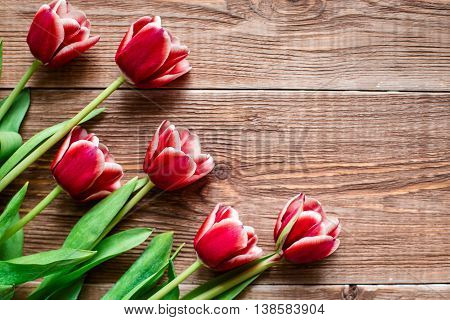 lovey red tulips. Flowers on wooden background. Copy space. Top view.