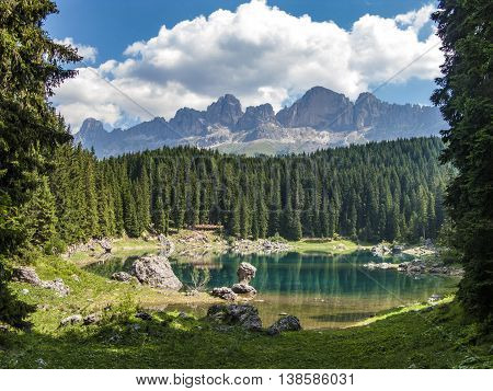 Perfectly clear emerald lake in Dolomites under cloudy sky