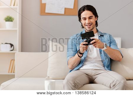 Playful mood. Cheerful delighted handsome man holding game console and playing video games while resting at home