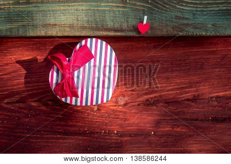 Gift box heart-shaped of striped wrapper with red ribbon bow decoration and heart clothespin on wooden plank on timber background