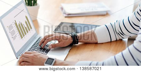 Working atmosphere. Pleasant man sitting at the table and using laptop while being involved in work in the office