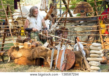 Monterenzio Italy 09 July 2016 - a wood carver craftsman  blacksmith realize swords and shields during a Celtic Festival