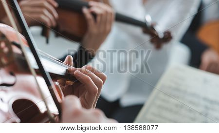 Violinist performing on stage with classical music symphony orchestra hands close up selective focus unrecognizable people