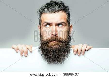 handsome bearded man with long lush beard and moustache on surprised face with white paper sheet in studio on grey background copy space