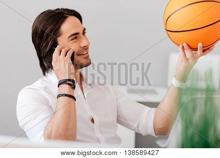 True player. Cheerful smiling bearded man holding basket ball and talking on cellphone while having a pleasant conversation