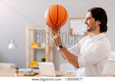 Masterful player. Pleasant joyful bearded man holding basket ball and holding it on the finger while standing in the office
