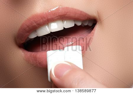 Closeup Detail Of Woman Putting Pink Chewing Gum Into Her Mouth