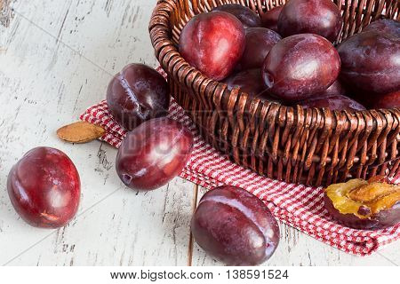 Ripe plums in a wicker basket on a napkin on a light wooden table.