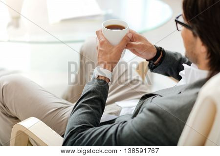 Far from reality. Pleasant relaxed man sitting in the chair and drinking tea while resting