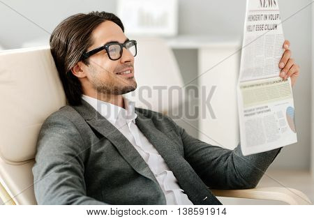 Pleasant relaxation. Cheerful content bearded man sitting in the armchair and reading newspaper while resting