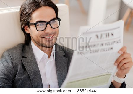 In whirlwind of news. Positive delighted smiling man sitting in the armchair and reading newspaper while resting