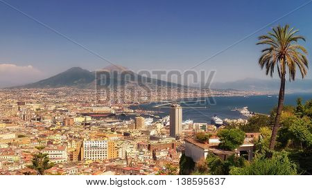 Panoramic view of the Gulf of Naples with the palaces the commercial port the cruise ships docked on the right and in the background the volcano Vesuvius.