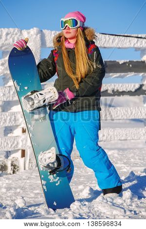 Snowboarder girl stands with snowboard. Sheregesh resort, Siberia, Russia