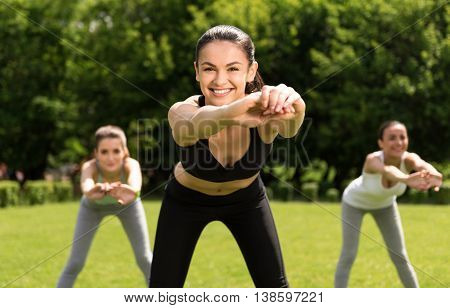 Best coach. Cheerful delighted beautiful woman holding hands together and doing sport exercises with her students while evincing gladness