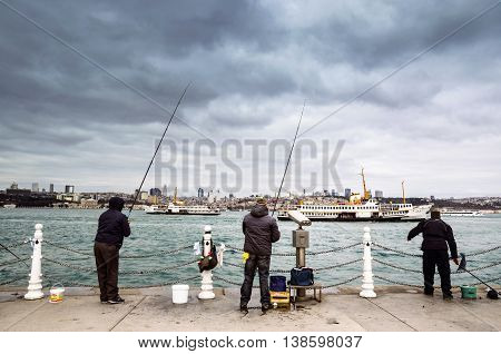 Istanbul Turkey - December 4 2013: Bosphorus Fishing Istanbul. Istanbul Asian side of the photo seen people fishing in the Uskudar district. In Istanbul particularly the differences in temperature and salinity between the Black Sea and the Mediterranean m