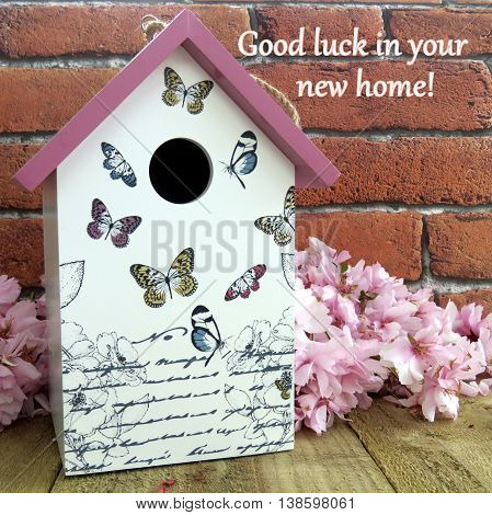 Decorative birdhouse with pink blossom on a wooden surface with 'good luck in your new home' text on brick effect background