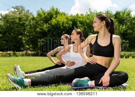 Refresh your mind. Cheerful content smiling women sitting on the rolling mat and stretching while doing sport activities in the park