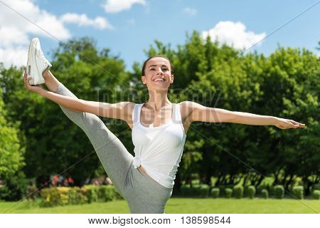 Share positivity. Cheerful smiling delighted attractive woman holding her leg up and expressing gladness while doing sport exercises