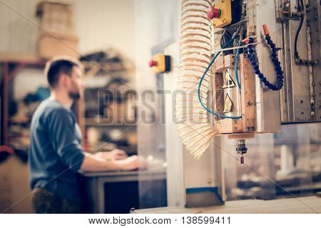 CNC machine against blurred background of employee operator
