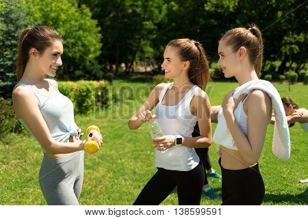 Pleasant conversation. Positive slim smiling women talking and expressing joy while resting after sport exercises