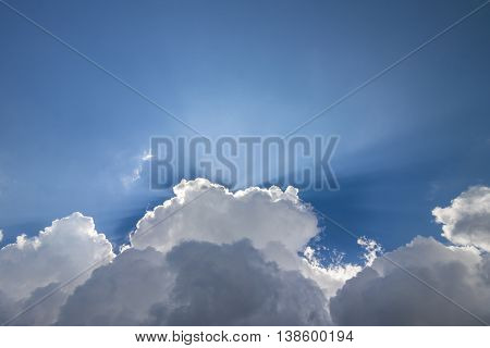Blue sky with puffy white clouds in bright clear sunny day