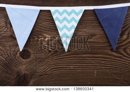 Party Triangle Bunting Flags Hanging On The Rope. On The Old Wooden Background.