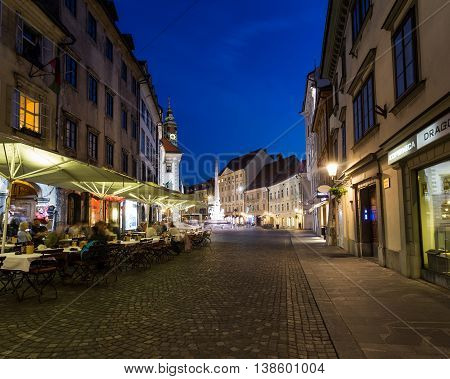 LJUBLJANA SLOVENIA - 26TH MAY 2016: The outside of buildings and streets in Town Square Ljubljana at night. People can be seen at local restaurants and on the streets.