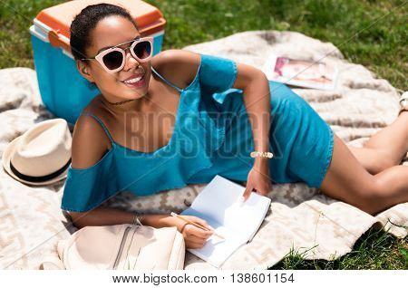 My day off. Happy and merry young woman making some notes while lying on the grass in the park and looking at a camera