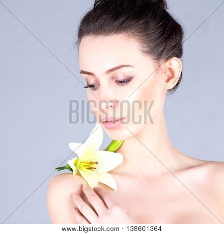Beauty brunette with blue eyes. Woman with clean and fresh skin looking down. Facial result.