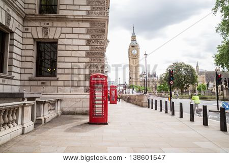 LONDON UK - 28TH JUNE 2016: A view towards Big Ben and Elizabeth Tower during the day. Red Telephone boxes and people can be seen in the foreground.