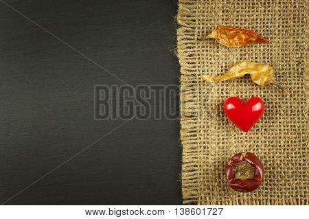 Old burlap on a black wooden board with dried chillies.