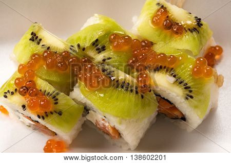 sushi and rolls with kiwi and salmon caviar close-up