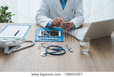 Professional doctor working at office desk he is using a smartphone healthcare and technology concept