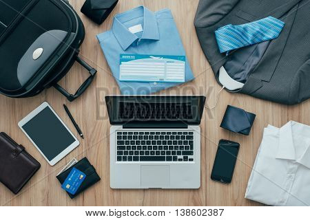 How to pack for a business trip: all items that needs to be packed a bag and a laptop on a desktop travel concept