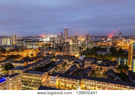 A view of apartment buildings towards the 02 Arena in East London at night
