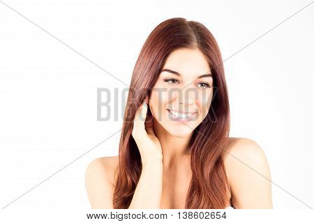 Happy smiling woman with straight red hair touching cheek. Skin care concept. Beauty woman.