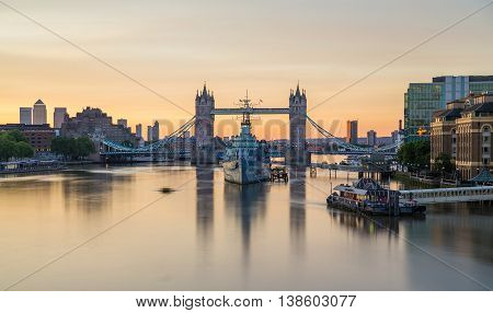 LONDON UK - 6TH JULY 2016: A view towards Tower Bridge and HMS Belfast in the morning. A colourful sky can be seen.