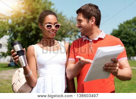 Nice walk. Cheerful young woman holding thermo cup and smiling young man pointing somewhere on his copybook while being together in the park
