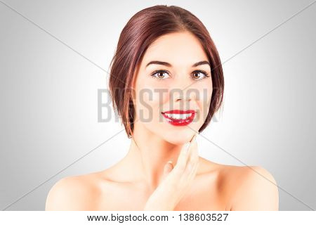 Woman with a perfect smile with white teeth. Sexy woman with red lips touching chin.