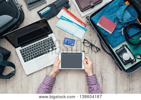 Traveler getting ready for a trip he is packing his bag and using a digital touch screen tablet flat lay