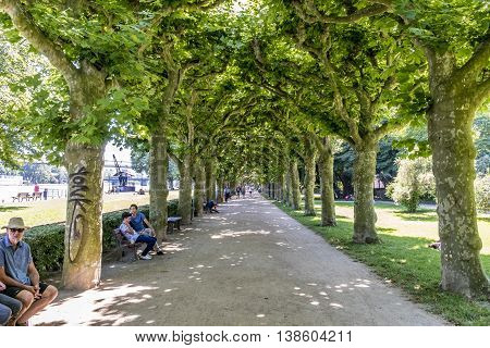 FRANKFURT GERMANY - JULY 10 2016: people relax at the benches in the area klein Nizza in Frankfurt Germany. This park area was established in 1910 and is a recreation area for public.