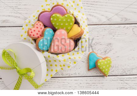 Colorful Valentine cookies in gift box on wooden background