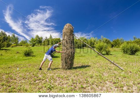 Young man pushing against a haystack on a sunny summer day