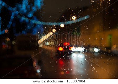 Wet the car window with the background of the night city lights