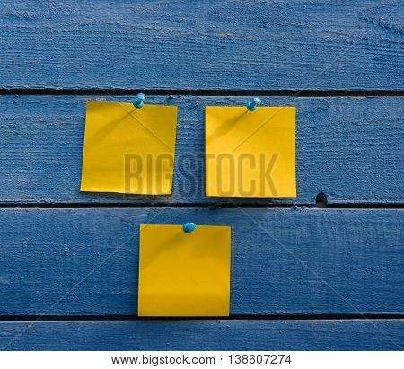 three yellow stickers on old blue wooden wall