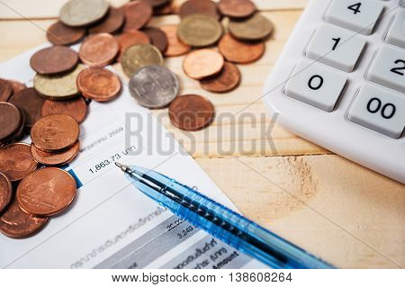 Bill with coins and pen and calculator on table Money for income and expenditure saving for dream