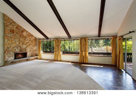 Spacious Unfurnished Living Room Interior With High Vaulted Ceiling And Stone Trim Fireplace