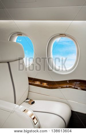 Aircraft jet porthole with clouds view, flight by business class
