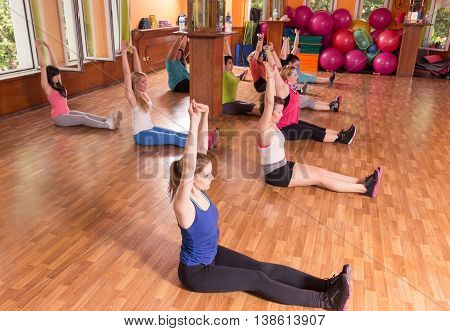 Group training girls sitting indoors hands arms up.